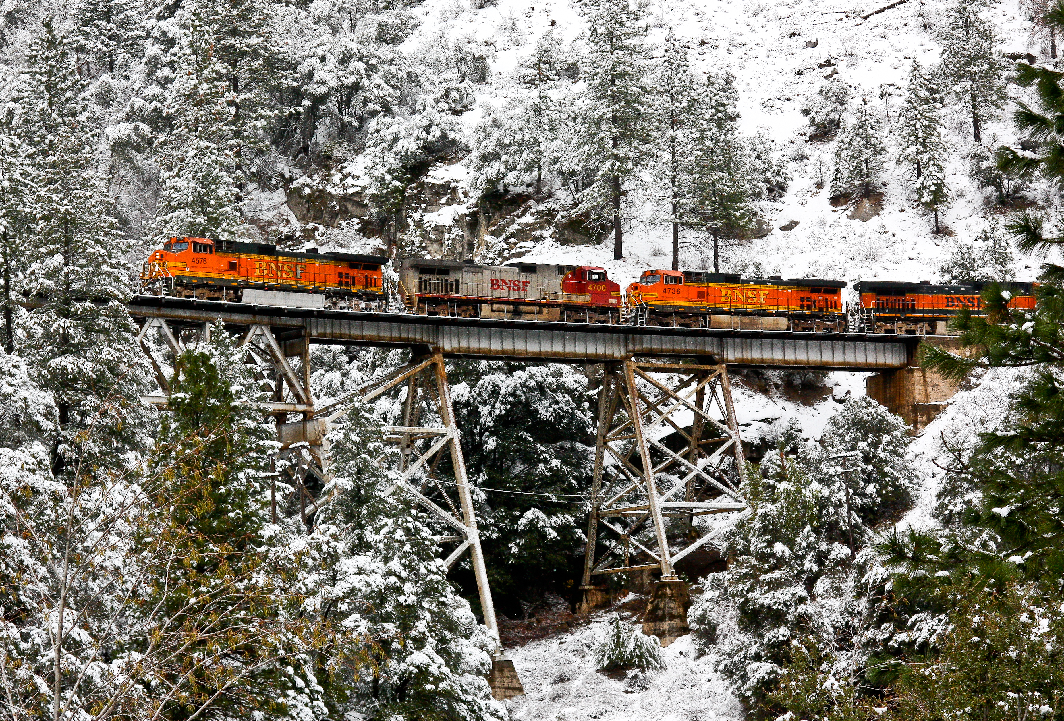 A BNSF train crosses the Rock Creek Trestle on a snowy day in the Feather River Canyon.