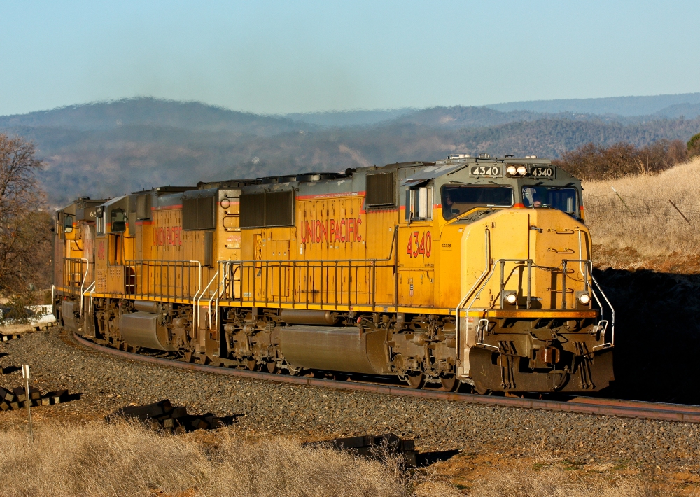 An ethanol train from the midwest rumbles through Oroville, California with the Sierra Nevada Mountains providing the backdrop.